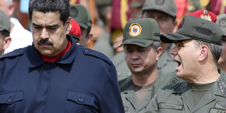 """Venezuelan President Nicolas Maduro (L) walks with Venezuelan Defense Minister Padrino Lopez (R) during a military parade in Caracas on December 12, 2015. Maduro asked Saturday the Armed Forces to get ready for an """"unconventional war"""", as he promised job betterments for the military. AFP PHOTO/JUAN BARRETO / AFP / JUAN BARRETO        (Photo credit should read JUAN BARRETO/AFP/Getty Images)"""