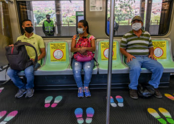 People wear face masks and sit on designated seats on a metro car as a preventive measure against the spread of the novel coronavirus COVID-19, in Medellin, Colombia, on May 4, 2020. - The novel coronavirus has killed at least 249,372 people worldwide since the outbreak first emerged in China last December, according to a tally from official sources compiled by AFP at 1900 GMT on Monday. (Photo by JOAQUIN SARMIENTO / AFP)