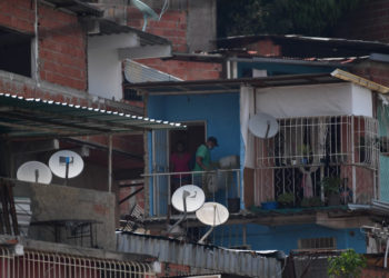 """View of DirecTV dish antennas installed on houses at the Petare neighborhood in Caracas on May 19, 2020. - US telecommunications giant AT&T announced on Tuesday its """"immediate"""" withdrawal from the pay television market in Venezuela, where it offered the DirecTV satellite platform, due to the impossibility of complying with the legal requirements of both countries. (Photo by Federico PARRA / AFP)"""