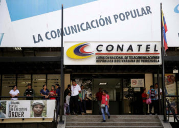 FILE PHOTO: A woman walks out from the building of the National Commission of Telecommunications (CONATEL), in Caracas, Venezuela February 16, 2017. REUTERS/Marco Bello/File Photo