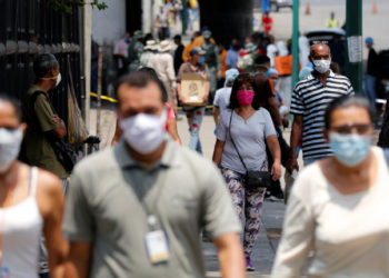 People wearing protective masks walk on a street during a nationwide quarantine as the spread of the coronavirus disease (COVID-19) continues, in Caracas, Venezuela April 20, 2020. REUTERS/Manaure Quintero