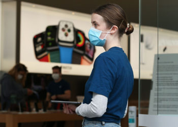 """An employee wears a protective mask at an Apple Inc. store reopening, after being closed due to lockdown measures imposed because of the coronavirus, in the Bondi Junction suburb of Sydney, Australia, on Thursday, May 7, 2020. Apple's app store saw its strongest month of growth in two and a half years in April, according to Morgan Stanley, which wrote that """"all major regions & categories saw accelerating spend"""" as a result of the pandemic. Photographer: Brendon Thorne/Bloomberg"""