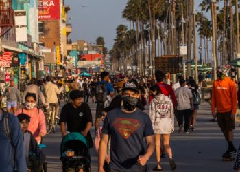 People walk at the boardwalk in Venice Beach during the first day of the Memorial Day holiday weekend amid the novel Coronavirus, COVID-19, pandemic in California on May 23, 2020. - Los Angeles County officials announced May 22, 2020, that beach bike paths and some beach parking lots will reopen and curbside service at indoor malls will be permitted. The county reopened its beaches a week ago but kept beach parking lots, bike paths, piers and boardwalks closed. (Photo by Apu GOMES / AFP)