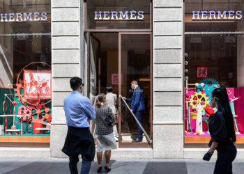 People line up to enter a Hermes luxury shop on May 18, 2020 in central Milan during the country's lockdown aimed at curbing the spread of the COVID-19 infection, caused by the novel coronavirus. - Restaurants and churches reopen in Italy on May 18, 2020 as part of a fresh wave of lockdown easing in Europe and the country's latest step in a cautious, gradual return to normality, allowing businesses and churches to reopen after a two-month lockdown. (Photo by Miguel MEDINA / AFP)