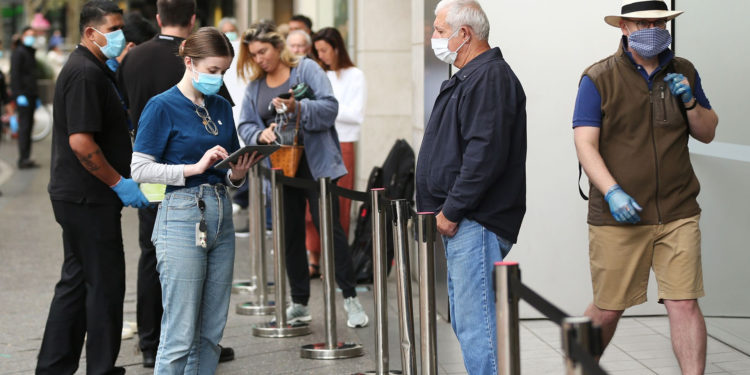 """An employee assists a customer, both wearing protective masks, waiting in-line at an Apple Inc. store reopening, after being closed due to lockdown measures imposed because of the coronavirus, in the Bondi Junction suburb of Sydney, Australia, on Thursday, May 7, 2020. Apple's app store saw its strongest month of growth in two and a half years in April, according to Morgan Stanley, which wrote that """"all major regions & categories saw accelerating spend"""" as a result of the pandemic. Photographer: Brendon Thorne/Bloomberg"""