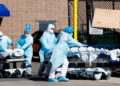 Healthcare workers transport two bodies past a construction worker building the interiors of one of two temporary morgues set up outside of the Wyckoff Heights Medical Center to handle the large number of victims of the COVID-19 disease in Brooklyn, New York, USA, 06 April 2020. EFE/EPA/JUSTIN LANE