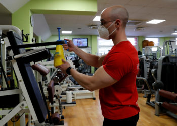 An instructor wearing a protective face mask disinfects equipment at a gym which has reopened with new social distancing and hygiene rules after months of closure due to an outbreak of the coronavirus disease (COVID-19), in Rome, Italy, May 25, 2020. REUTERS/Remo Casilli