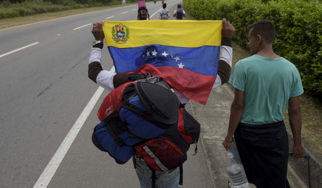 """A Venezuelan migrant holding a national flag walks with other migrants on the road from Cucuta to Pamplona, in Norte de Santander Department, Colombia, on February 10, 2019. - Opposition leader Juan Guaido, recognized by some 50 countries as Venezuela's interim president, warned the military Sunday that blocking humanitarian aid from entering the country is a """"crime against humanity."""" (Photo by Raul ARBOLEDA / AFP)"""