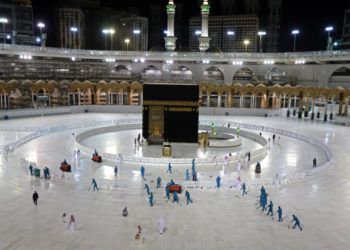 """(FILES) In this file photo taken on April 24, 2020, sanitation workers disinfect the area around the Kaaba in Mecca's Grand Mosque, on the first day of the Islamic holy month of Ramadan, amid unprecedented bans on family gatherings and mass prayers due to the coronavirus (COVID-19) pandemic. - Saudi Arabia announced it would hold a """"very limited"""" hajj this year owing to the coronavirus pandemic, with pilgrims already in the kingdom allowed to take part. (Photo by STR / AFP)"""