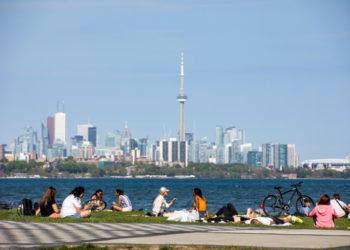 FILE PHOTO: People maintain social distance as they sit at Humber Bay Shores park while the province prepares for more phased re-openings from the coronavirus disease (COVID-19) restrictions in Toronto, Ontario, Canada May 24, 2020. REUTERS/Carlos Osorio/File Photo