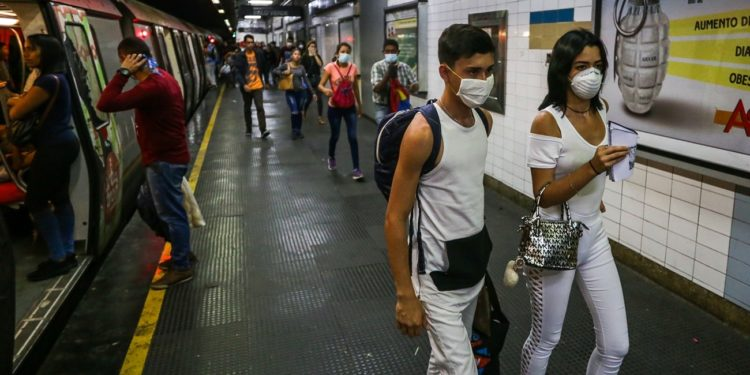 People travel on the subway wearing protective masks as a preventive measure in the face of the global COVID-19 coronavirus pandemic, in Caracas, on March 14, 2020. - Venezuela requires a 'mandatory quarantine' for all travelers from Europe who arrived in the country in March, one day after confirming their first two cases of coronavirus. (Photo by Cristian Hernandez / AFP)