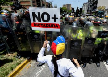 Opposition activists protest against President Nicolas Maduro's government in Caracas on April 4, 2017.  Activists clashed with police in Venezuela Tuesday as the opposition mobilized against moves to tighten President Nicolas Maduro's grip on power. Protesters hurled stones at riot police who fired tear gas as they blocked the demonstrators from advancing through central Caracas, where pro-government activists were also planning to march. / AFP PHOTO / FEDERICO PARRA