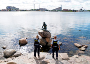 Copenhagen (Denmark), 03/07/2020.- Police officers take pictures of the iconic 'Little Mermaid' statue after the rock that serves as its plinth appeared with the message 'Racist Fish' in English spraypainted on it overnight in Copenhagen, Denmark, 03 July 2020. The bronze statue, created by sculptor Edvard Eriksen in 1913 based on the homonymous fairytale by Hans Christian Andersen, is one of the Danish capital's biggest tourist attractions. Over the past decades, it has been subjected to vandalism (decapitation, graffiti, defacement, etc.) numerous times. (Protestas, Abierto, Dinamarca, Copenhague) EFE/EPA/MADS CLAUS RASMUSSEN DENMARK OUT