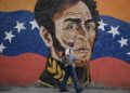 A man wearing a face mask walks past a mural depicting South American independence hero Simon Bolivar in Caracas on April 17, 2020, amid the novel coronavirus (COVID-19) outbreak. - The health emergency due to the new coronavirus in Venezuela reinforced Nicolas Maduro's internal control and neutralized Juan Guaido, making him more dependant on his international allies, just when the opposition tried to reactivate its offensive against the socialist government. (Photo by Federico Parra / AFP) (Photo by FEDERICO PARRA/AFP via Getty Images)