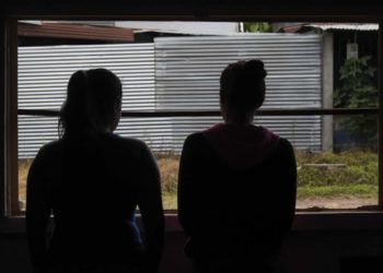 Venezuelan sex workers Joli (L), 35, and her niece Milagro, 19, look through a window during an interview with AFP at a bar in Calamar municipality, Guaviare department, Colombia on October 11, 2018. - Venezuelan migrants who fled their country due to the crisis, turn to prostitution in Colombia for the lack of opportunities to work in other trades. (Photo by Raul ARBOLEDA / AFP)
