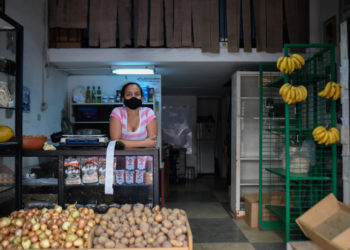 "An employee waits for customers at a photography store now selling food, due to the COVID-19 coronavirus pandemic, in Chacao neighborhood in Caracas on July 15, 2020, amid the coronavirus pandemic. - The COVID-19 pandemic, which reached Venezuela in mid-March and has infected some 10,000 people, according to official figures, forced the closure of 90% of the businesses in the Caribbean country, according to the private company Consecomercio. Only supermarkets, pharmacies and other businesses considered ""essential"" by the socialist government are exempted from the national quarantine, which has been tightened in Caracas due to the spread of the virus. (Photo by Federico PARRA / AFP)"