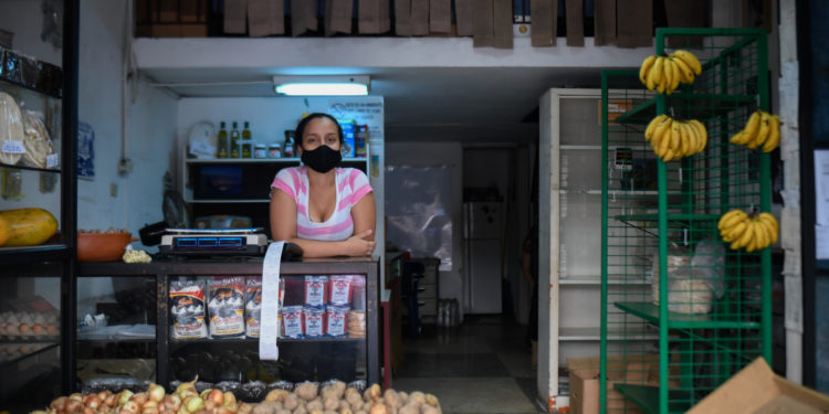 """An employee waits for customers at a photography store now selling food, due to the COVID-19 coronavirus pandemic, in Chacao neighborhood in Caracas on July 15, 2020, amid the coronavirus pandemic. - The COVID-19 pandemic, which reached Venezuela in mid-March and has infected some 10,000 people, according to official figures, forced the closure of 90% of the businesses in the Caribbean country, according to the private company Consecomercio. Only supermarkets, pharmacies and other businesses considered """"essential"""" by the socialist government are exempted from the national quarantine, which has been tightened in Caracas due to the spread of the virus. (Photo by Federico PARRA / AFP)"""