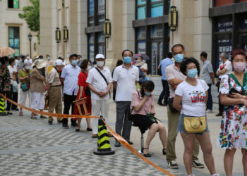 People line up to undergo COVID-19 coronavirus tests at a makeshift testing center in Dalian, in China's northeast Liaoning province on July 27, 2020. - China recorded 61 new coronavirus cases on July 27 -- the highest daily figure since April -- propelled by clusters in three separate regions that have sparked fears of a fresh wave. (Photo by STR / AFP) / China OUT