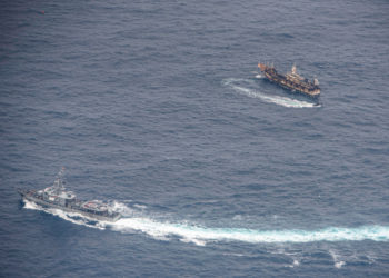 Ecuadorian Navy vessels surround a fishing boat after detecting a fishing fleet of mostly Chinese-flagged ships in an international corridor that borders the Galapagos Islands' exclusive economic zone, in the Pacific Ocean, August 7, 2020. Picture taken August 7, 2020.  REUTERS/Santiago Arcos