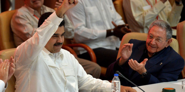 Venezuelan President Nicolas Maduro (L) and Cuban President Raul Castro (C) gesture and clap during the closing ceremony of the XVI Political Council of the Bolivarian Alliance for the People of Our Americas (ALBA) at the Convention Palace in Havana, on December 14, 2017. / AFP PHOTO / YAMIL LAGE        (Photo credit should read YAMIL LAGE/AFP/Getty Images)