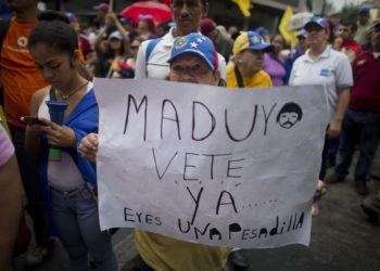 "A woman holds a sign with a message that reads in Spanish: ""Maduro leave already......you are a nightmare!"" during an opposition march in Caracas, Venezuela, Saturday, May 14, 2016. The protesters are demanding that electoral officials accelerate the certification of the petition signatures that would kick off a recall of President Nicolas Maduro. (AP Photo/Ariana Cubillos)"