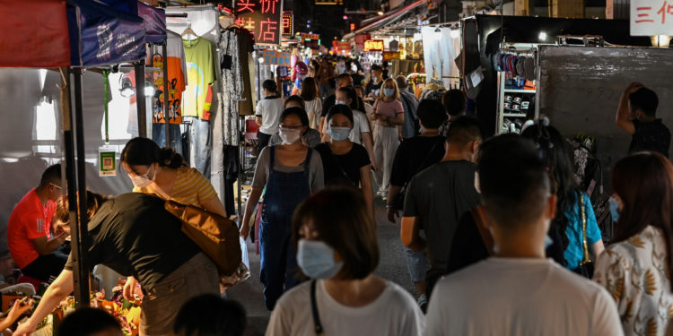 This photo taken on August 6, 2020 shows people walking around a night market in Wuhan in China's central Hubei province. - The city's convalescence since a 76-day quarantine was lifted in April has brought life and gridlocked traffic back onto its streets, even as residents struggle to find their feet again. Long lines of customers now stretch outside breakfast stands, a far cry from the terrified crowds who queued at city hospitals in the first weeks after a city-wide lockdown was imposed in late January to curb the spread of the COVID-19 coronavirus. (Photo by Hector RETAMAL / AFP)
