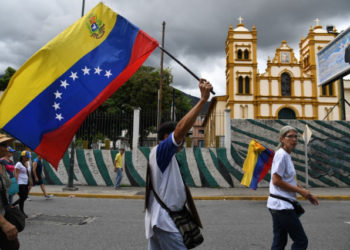 Venezuela's opposition supporters march with a Venezuelan national flag from the UN development program headquarters to the Military Counterintelligence General Directorate (DGCIM) headquarters in Caracas on July 5, 2019, during the anniversary of the Venezuelan Independence. (Photo by Yuri CORTEZ / AFP)