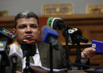 Lawmaker Luis Parra holds a miniature copy of the Venezuelan constitution as he gives a press conference at the National Assembly in Caracas, Venezuela, Monday, Jan. 6, 2020. The previous day, lawmakers loyal to President Nicolas Maduro rushed to choose Parra as their new legislative president, while many opposition lawmakers were blocked from entering the voting session. (AP Photo/Andrea Hernandez Briceño)