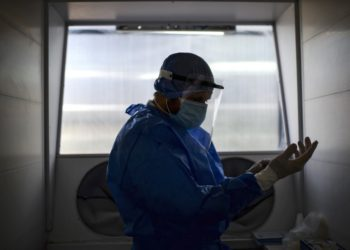 A doctor gets ready to take a swab sample through a protection system at the Professor Alejandro Posadas National Hospital in the municipality of El Palomar, province of Buenos Aires, on September 18, 2020, amid the COVID-19 novel coronavirus pandemic. - The pandemic has killed at least 946,727 people worldwide, including more than 12,000 in Argentina, since emerging in China late last year, according to an AFP tally at 1100 GMT Friday based on official sources. (Photo by Ronaldo SCHEMIDT / AFP)