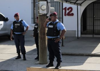 """Members of the National Police stand outside """"Canal 12"""" television station where they requisited its workers, in Managua on January 24, 2019. - Nicaraguan authorities denied Wednesday that they had suspended the transmission of three television programs critical with the government of Daniel Ortega, following the denunciation of journalist Carlos Fernando Chamorro, who had described the measure as an """"abuse of power"""". The Nicaraguan Telecommunications and Post Office (TELCOR) issued a statement at the end of the afternoon stating that """"it has not ordered the cancellation of any program"""" and described the news as """"totally false"""". (Photo by Inti OCON / AFP)"""