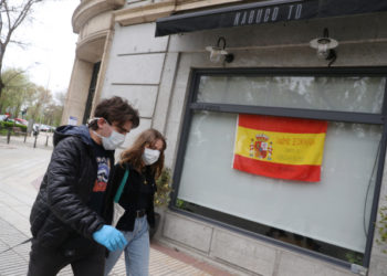 "Marco Donoso del Bufalo, 20, a young man on the autism spectrum, and his sister Irene, 22, walk past a Spanish flag that reads ""Come on, Spain. Together we will succed"" as they take their daily walk during the lockdown amid the coronavirus disease (COVID-19) outbreak in Madrid, Spain, April 9, 2020. Picture taken April 9, 2020. REUTERS/Susana Vera"