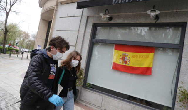 """Marco Donoso del Bufalo, 20, a young man on the autism spectrum, and his sister Irene, 22, walk past a Spanish flag that reads """"Come on, Spain. Together we will succed"""" as they take their daily walk during the lockdown amid the coronavirus disease (COVID-19) outbreak in Madrid, Spain, April 9, 2020. Picture taken April 9, 2020. REUTERS/Susana Vera"""