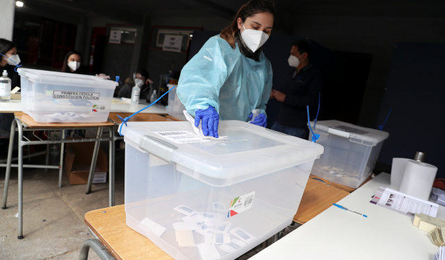 A woman wearing a protective face mask and a suit disinfects a ballot box during a referendum on a new Chilean constitution in Santiago, Chile, October 25, 2020. REUTERS/Ivan Alvarado