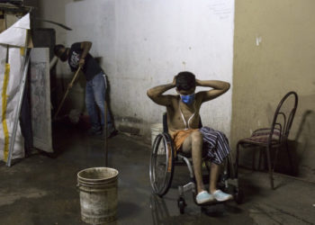 Johan Medina (R), 31, puts on a face mask after taking a bath, as one of his neighbors (L) sweeps dirty water to a drain at a shelter located in the basement of the Sudameris public building in Caracas, on October 9, 2020, amid the new coronavirus pandemic. - Fourteen families live without electricity, ventilation, running water or bathrooms in the basement of a government building in Caracas, which makes them specially vulnerable to the coronavirus. (Photo by Cristian Hernandez / AFP)