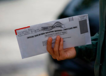 "A woman holds a vote-by-mail ballot outside Miami Beach City Hall in Miami Beach, Florida on October 19, 2020. - President Donald Trump lashed out at ""stupid"" critics from within his own party and called for unity on Sunday after growing Republican criticism and warnings of a ""bloodbath"" in the November 3 election. Trump issued the comments as he and his Democratic opponent Joe Biden hit the ground in crucial swing states in the final stretch before an election that opinion polls show the real estate mogul is at serious risk of losing. (Photo by Eva Marie UZCATEGUI / AFP) (Photo by EVA MARIE UZCATEGUI/AFP via Getty Images)"
