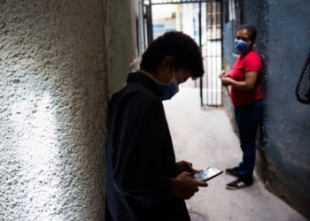 Jhonatan Figueroa, 14, uses his cellphone, connected to a neighbour's wifi signal, outside his home, as his mother Viviana Rodriguez looks at him, at the Bello Campo neighborhood in Chacao, Caracas, on October 6, 2020, amid the new coronavirus pandemic. - With students that have to catch internet in the streets and teachers who earn 2,5 US dollars a month, classes start up again in Venezuela. (Photo by Cristian Hernandez / AFP)