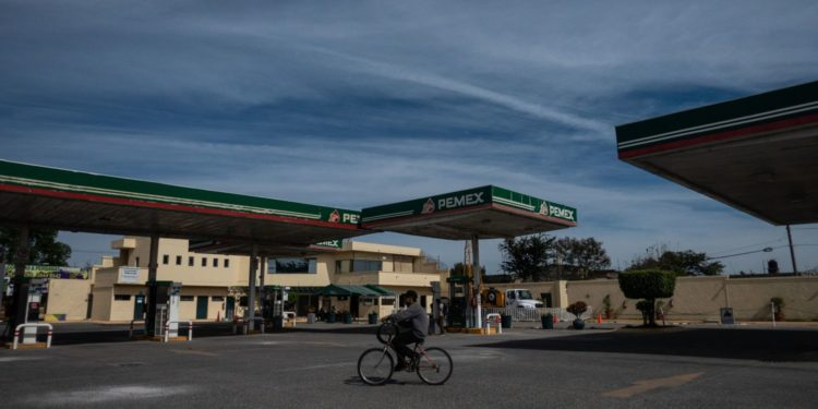 A person rides a bicycle in front of a Petroleos Mexicanos (Pemex) gas station closed amid a fuel shortage in Zapopan, Jalisco state, Mexico, on Monday, Jan. 7, 2018. Mexico's new government has sought to assure worried consumers that its fuel theft plan is working while cars waited hours to fuel up over the weekend and gasoline tankers swarmed congested ports. Photographer: Cesar Rodriguez/Bloomberg