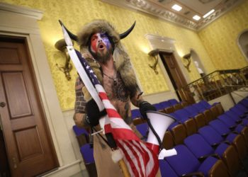 "WASHINGTON, DC - JANUARY 06: A protester screams ""Freedom"" inside the Senate chamber after the U.S. Capitol was breached by a mob during a joint session of Congress on January 06, 2021 in Washington, DC. Congress held a joint session today to ratify President-elect Joe Biden's 306-232 Electoral College win over President Donald Trump. A group of Republican senators said they would reject the Electoral College votes of several states unless Congress appointed a commission to audit the election results. Pro-Trump protesters entered the U.S. Capitol building during demonstrations in the nation's capital. Win McNamee/Getty Images/AFP == FOR NEWSPAPERS, INTERNET, TELCOS & TELEVISION USE ONLY =="