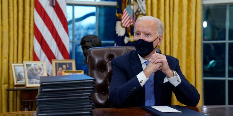 President Joe Biden waits to sign his first executive order in the Oval Office of the White House on Wednesday, Jan. 20, 2021, in Washington. (AP Photo/Evan Vucci)
