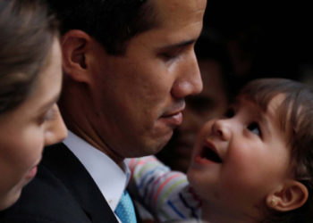 Venezuelan opposition leader and self-proclaimed interim president Juan Guaido pauses as he speaks to the media next to his wife Fabiana Rosales, while carrying their daughter outside their home after a meeting with supporters to present a government plan of the opposition in Caracas, Venezuela January 31, 2019. REUTERS/Carlos Barria