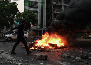 A protester walk past a burning makeshift barricade along a road during a protest against the military coup, in Yangon on March 30, 2021. (Photo by STR / AFP)