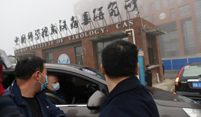 Members of the World Health Organization (WHO) team investigating the origins of the COVID-19 coronavirus arrive by car at the Wuhan Institute of Virology in Wuhan in China's central Hubei province on February 3, 2021. (Photo by HECTOR RETAMAL / AFP)