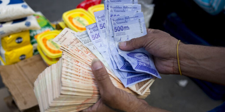 A man holds Bolivar bills a street market in Caracas' Catia neighborhood, on April 6, 2021, amid the Covid-19 pandemic. (Photo by Pedro Rances Mattey / AFP)