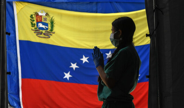 A staff member of Doctors Without Borders prepares herself waits for patients to be tested for COVId-19 in front of a Venezuelan flag at the Perez de Leon Hospital os the Petare neighbourhood, in eastern Caracas on June 23, 2020, amid the new coronavirus pandemic. - In Petare, the largest slum in Venezuela, more than 100 professionals of Doctors Without Borders face the COVID-19 pandemic getting around the crisis in the country's public healthcare sector. (Photo by Federico PARRA / AFP)