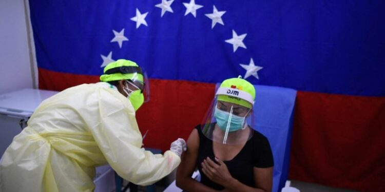 A health worker administers a dose of the Sputnik V vaccine against COVID-19 to a staff member of the Perez de Leon Hospital in Petare neighbourhood, in eastern Caracas, on February 19, 2021, amid the novel coronavirus pandemic. (Photo by Federico PARRA / AFP)