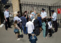 People gather by the fence of School No. 175 following a shooting in Kazan on May 11, 2021. (Photo by Roman Kruchinin / AFP)