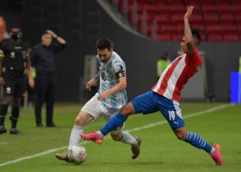 Argentina's Lionel Messi (L) and Paraguay's Santiago Arzamendia vie for the ball during their Conmebol Copa America 2021 football tournament group phase match at the Mane Garrincha Stadium in Brasilia on June 21, 2021. (Photo by NELSON ALMEIDA / AFP)