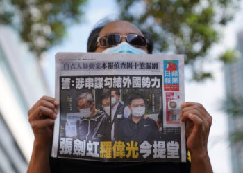A supporter holds a copy of Apple Daily newspaper during a court hearing outside West Magistrates' Courts, after police charge two executives of the pro-democracy Apple Daily newspaper over the national security law, in Hong Kong, China, June 19, 2021. REUTERS/Lam Yik