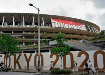 Tokyo (Japan), 23/06/2021.- (FILE) - Passersby walk past the National Stadium, the main stadium of the 2020 Tokyo Olympic Games, in Tokyo, Japan, 23 June 2021 (reissued 17 July 2021). According to a statement from the Tokyo 2020 Organising Committee, a person staying within the Olympic Village tested positive for COVID-19, and was subsequently placed in 14 day quarentine. (JapÛn, Tokio) EFE/EPA/FRANCK ROBICHON
