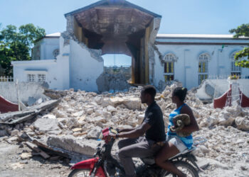 """People drive past the remains of the """"Sacré coeur des Cayes"""" church in Les Cayes on August 15, 2021, after a 7.2-magnitude earthquake struck the southwest peninsula of the country. - Hunched on benches, curled up in chairs or even lying the floor, those injured in the powerful earthquake that wreaked havoc on Haiti on Saturday crowded an overburdened hospital near the epicenter. The emergency room in Les Cayes, in southwestern Haiti, which was devastated by the 7.2-magnitude quake on Saturday morning that killed at least 724 people, is expecting reinforcements to help treat some of the thousands of injured. (Photo by Reginald LOUISSAINT JR / AFP)"""
